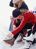 Mother and daughter (12-13) lacing up ice skates, elevated view
