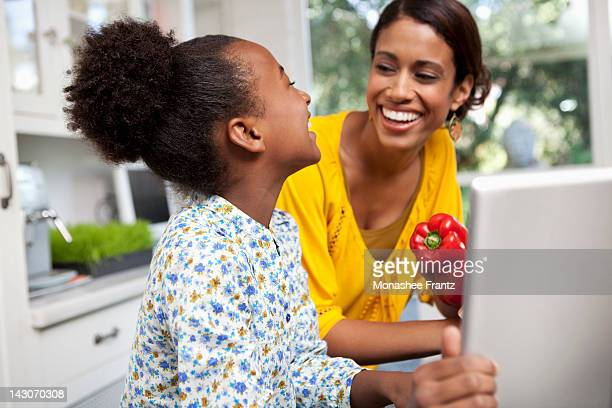 Mother and daughter laughing in kitchen