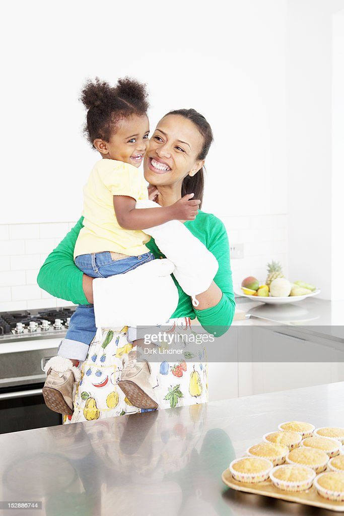 Mother and daughter laughing in kitchen : Stock Photo