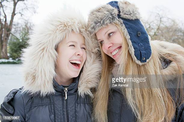 Mother and daughter laughing in snow