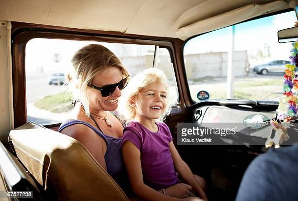 Mother and daughter laughing sitting in car