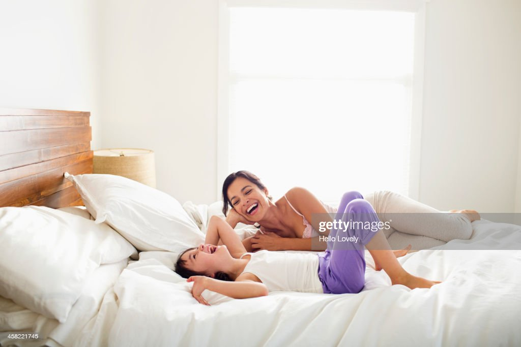 Mother and daughter laying in bed : Stock Photo