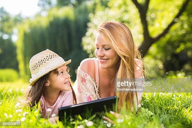 Mutter und Tochter Leg dich im Gras halten Digitaltablett.