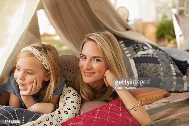 Mother and daughter laying in tent outdoors