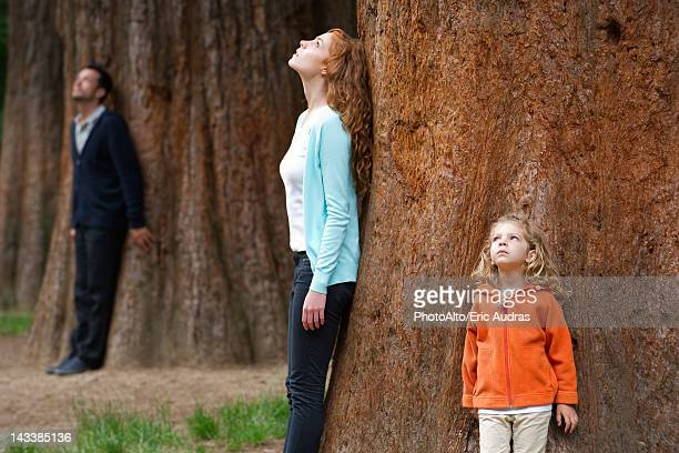 Mother and daughter leaning against tree trunk, breathing fresh air