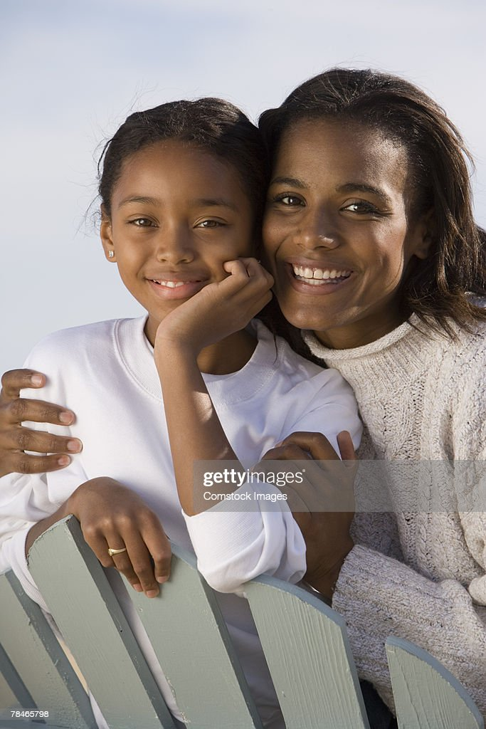 Mother and daughter leaning on back of adirondack chair : Stock Photo