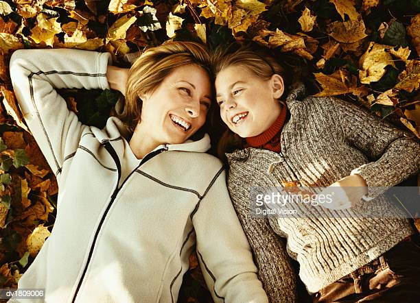 Mother and Daughter Lie Side by Side on Autumn Leaves, Laughing