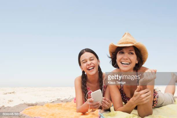 Mother and daughter listening to headphones on beach