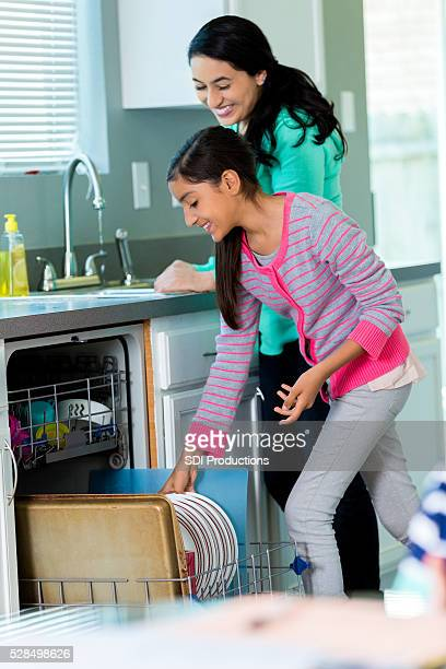 Mother and daughter load dishwasher