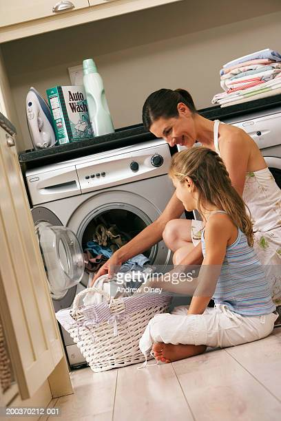 Mother and daughter (7-9) loading washing machine, smiling