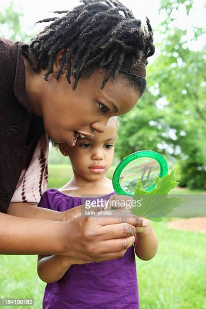 Mother and daughter look at leaf through magnifying glass