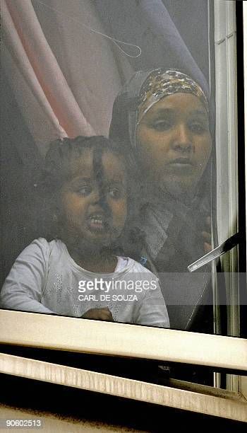 A mother and daughter look out of the window as they watch anti muslim protestors being arrested by the police in Harrow North London on September 11...
