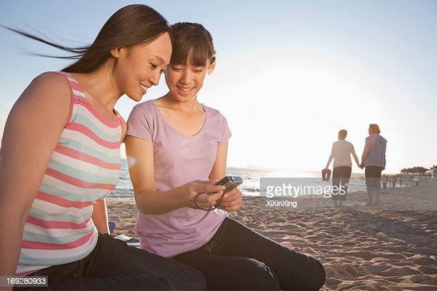 Mother and Daughter looking at camera on the beach