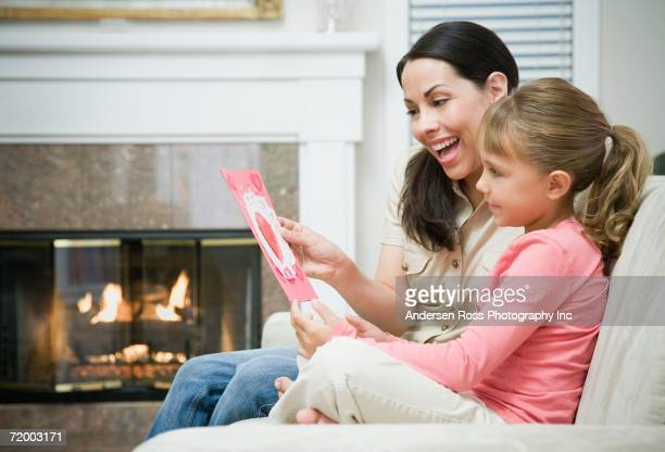 Mother and daughter looking at card on sofa