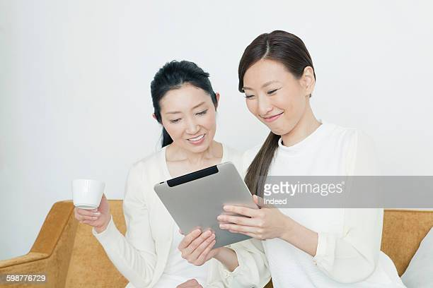 Mother and daughter looking at digital tablet on sofa