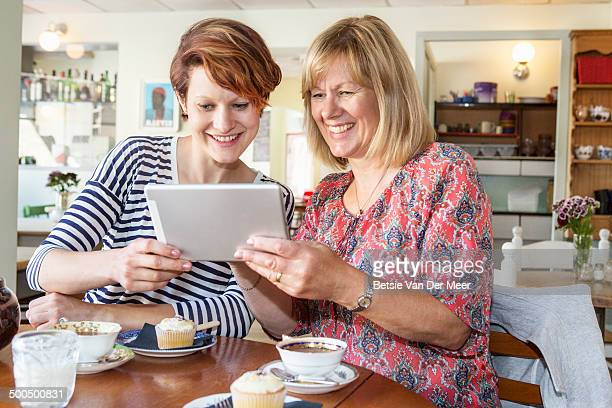 Mother and daughter looking at digital tablet..