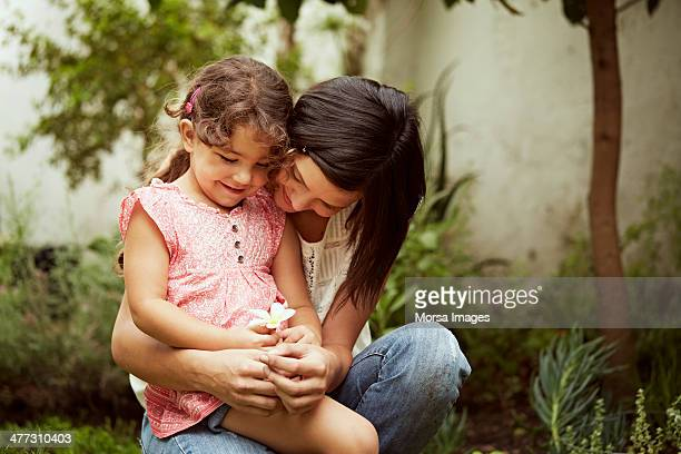 Mother and daughter looking at flower