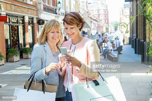 mother and daughter looking at mobile phone.