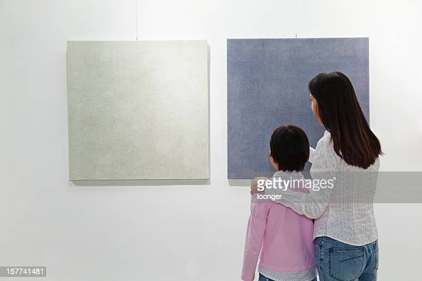 Mother and daughter looking at painting in an art gallery