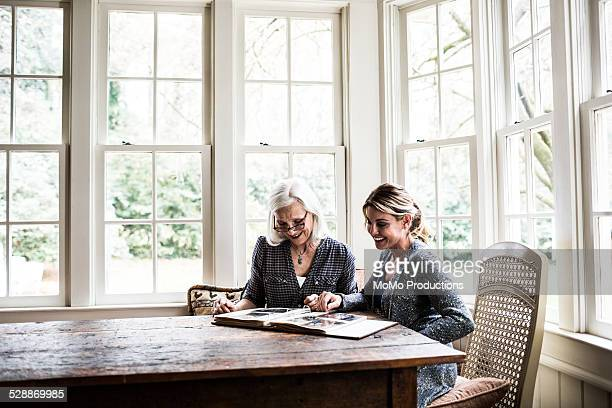 Mother and daughter looking at photo album