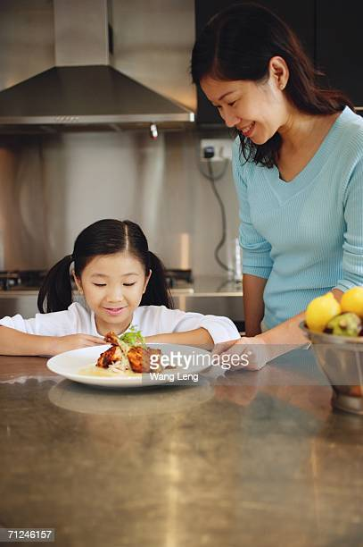 Mother and daughter looking at plate of food, smiling