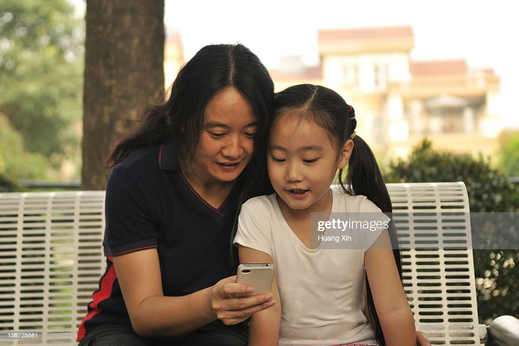 Mother and Daughter Looking at Smart Phone : Stock Photo