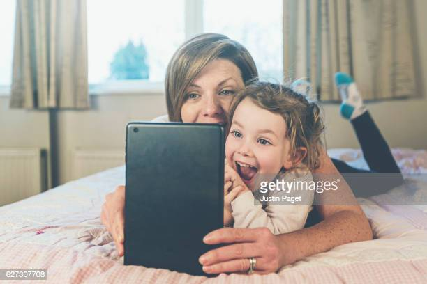 Mother and Daughter looking at tablet computer on bed
