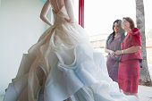 Mother and daughter looking at wedding dress in shop window