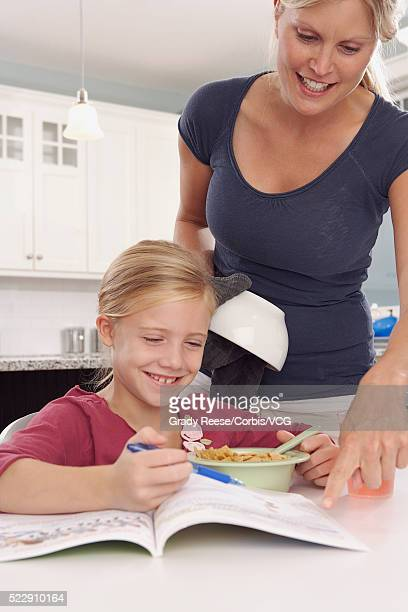 Mother and daughter looking at workbook together