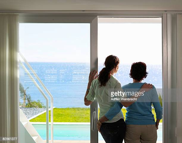 Mother and daughter looking out to sea