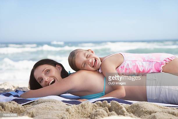 A mother and daughter lying on a beach towel happily embracing