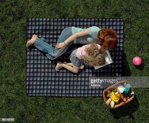 A mother and daughter lying on a blanket on the grass and reading a book