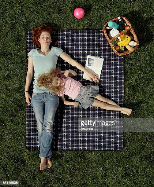 A mother and daughter lying on a blanket on the grass resting