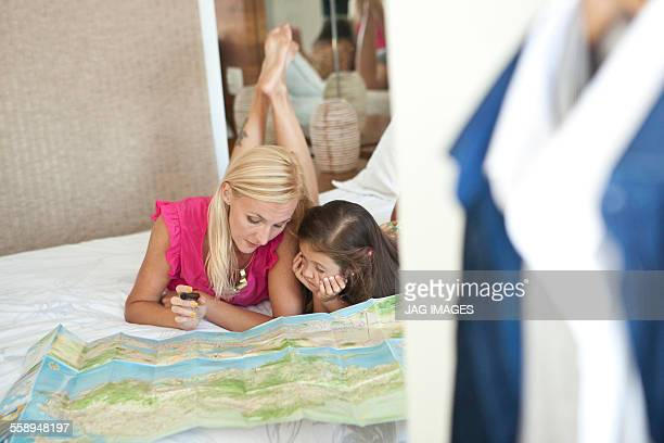 Mother and daughter lying on bed, looking at map