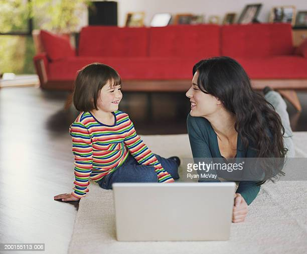 Mother and daughter (2-4) lying on floor, using laptop, smiling