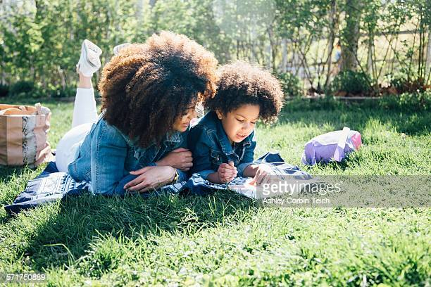 Mother and daughter lying on fronts, side by side, reading book together