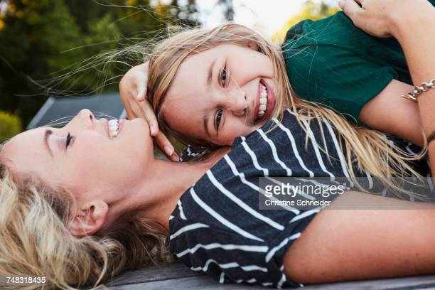 Mother and daughter lying on wooden decking outdoors