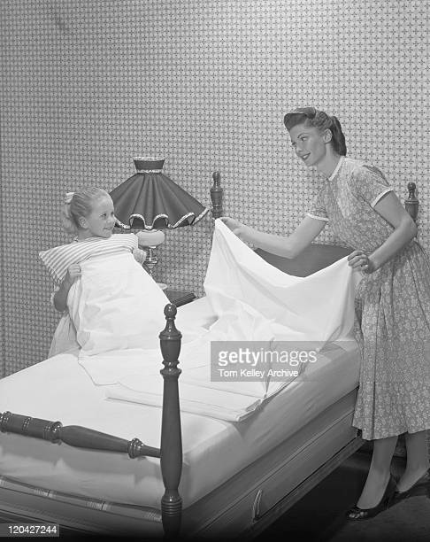 Mother and daughter making bed together, smiling