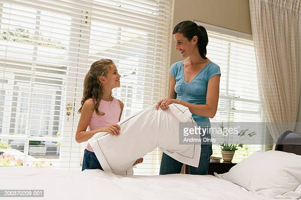 Mother and daughter (7-9) making bed together, smiling