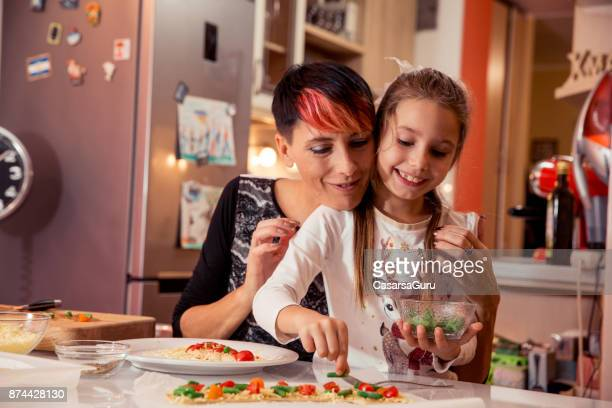 Mother and Daughter Making Christmas Pizza Together
