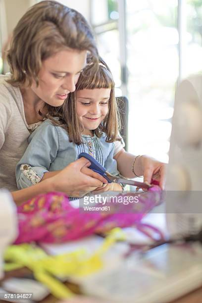Mother and daughter making clothes at home