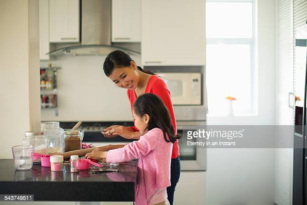 Mother and daughter making cookies in kitchen