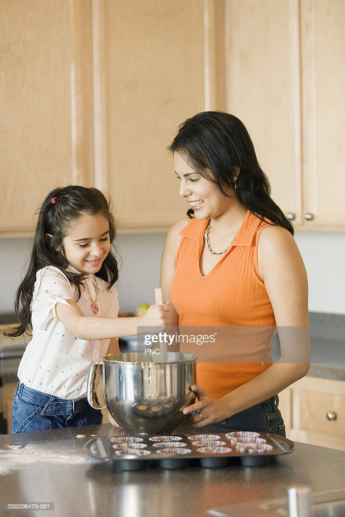 Mother and daughter (4-6) making cupcake batter in domestic kitchen : Stock Photo
