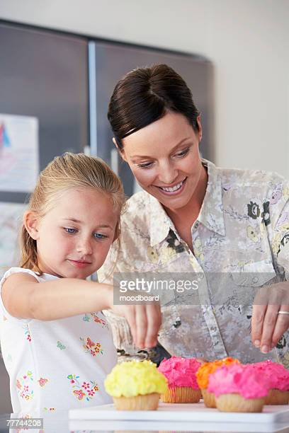 mother and daughter making cupcakes