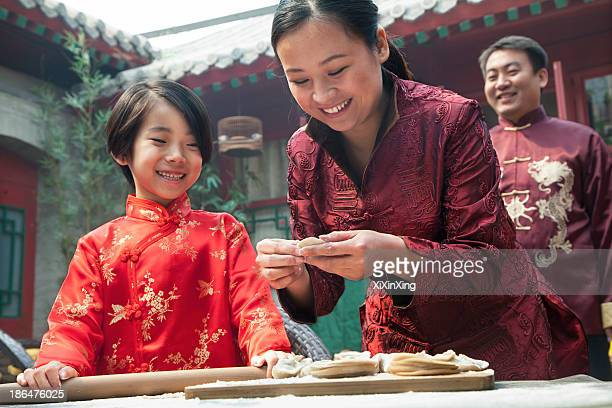 Mother and daughter making dumplings in traditional clothing