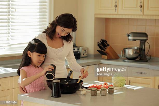 Mother and daughter making food together