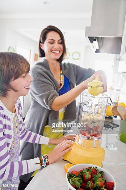 Mother and daughter making fruit smoothie