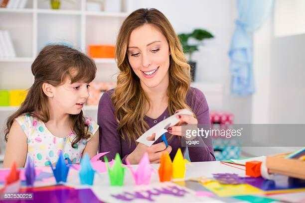 Mãe e filha fazendo origami.