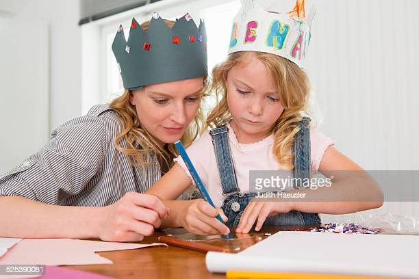 Mother and daughter making paper crowns