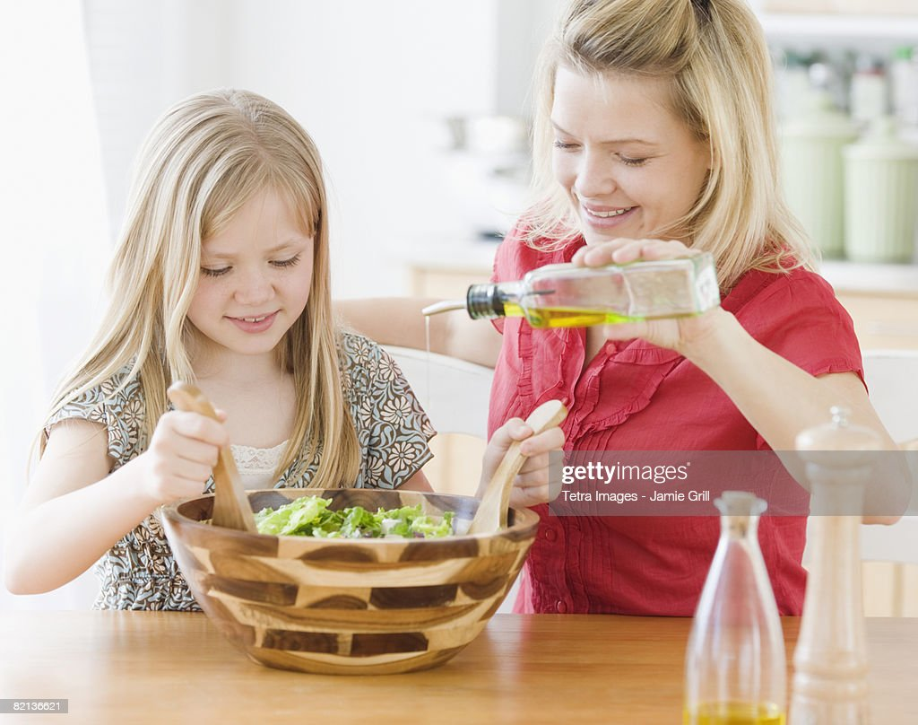 Mother and daughter making salad : Stock Photo